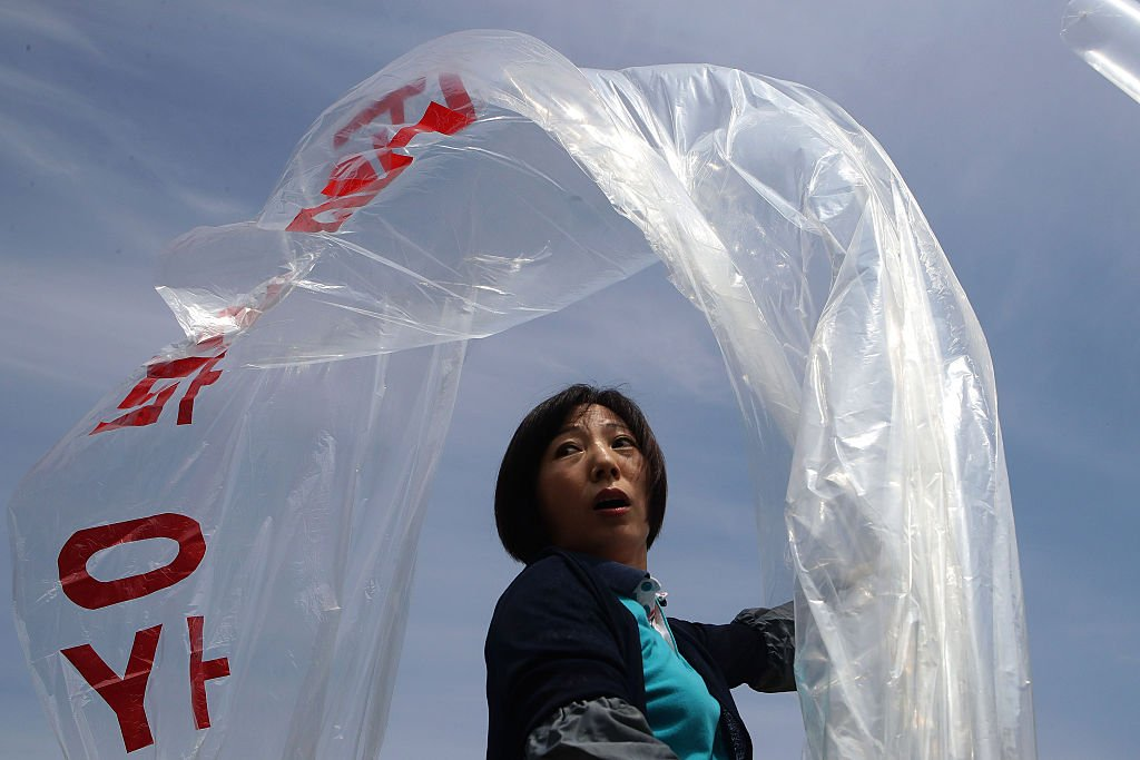 A woman holding a balloon with Korean writing on it