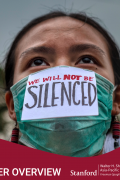 """Woman with facemask that says """"We will not be silenced"""""""