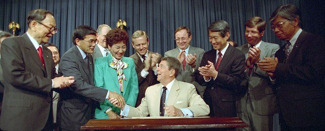 President Reagan shaking hands with Norman Mineta after signing the Civil Liberties Act of 1988