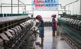 Women work a silk factory beneath a banner with Korean writing.