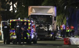 Police officers and rescue workers stand near the truck that Mohamed Lahouaiej Bouhlel drove into a crowd leaving a fireworks display in the French Riviera town of Nice on July 14, 2016, killing at least 84 people.