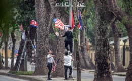 Workers remove the U.S flag from a display that was erected for the DPRK-USA summit, ahead of the arrival of North Korean leader Kim Jong-un at the Presidential Palace on March 1, 2019 in Hanoi, Vietnam