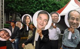 People hold pictures of Taiwanese presidential candidates