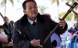 Man smokes while playing an erxian