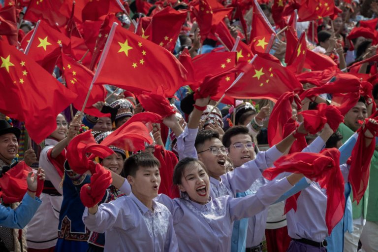 Chinese participants wave the national flag as they in a parade to celebrate the 70th Anniversary of the founding of the People's Republic of China in 1949, at Tiananmen Square on October 1, 2019 in Beijing, China.