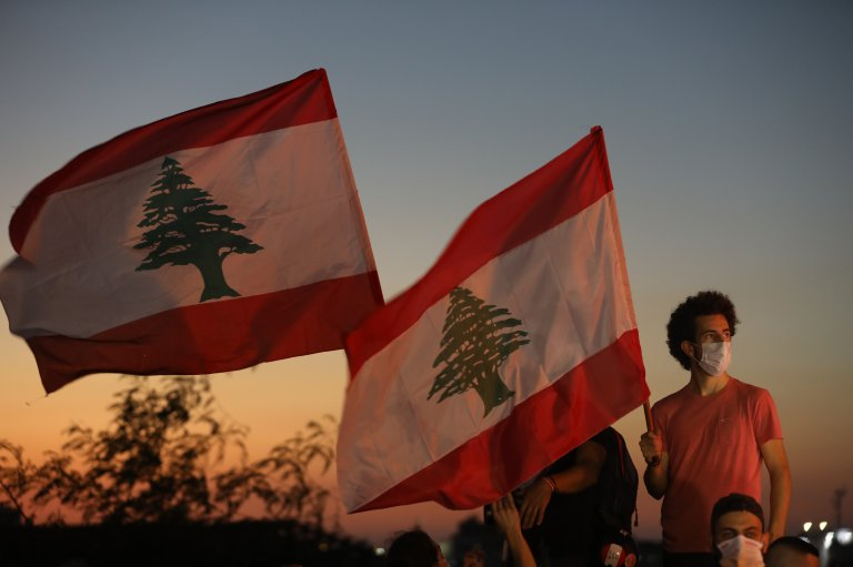 Picture of Lebanese protester in Mask with two flags.