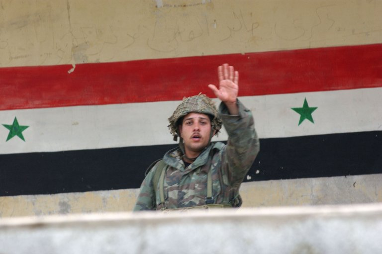 Soldier in front of Syrian flag