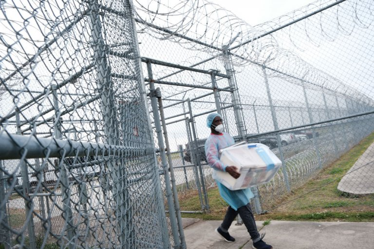A health-care worker carries COVID-19 vaccines into a prison.