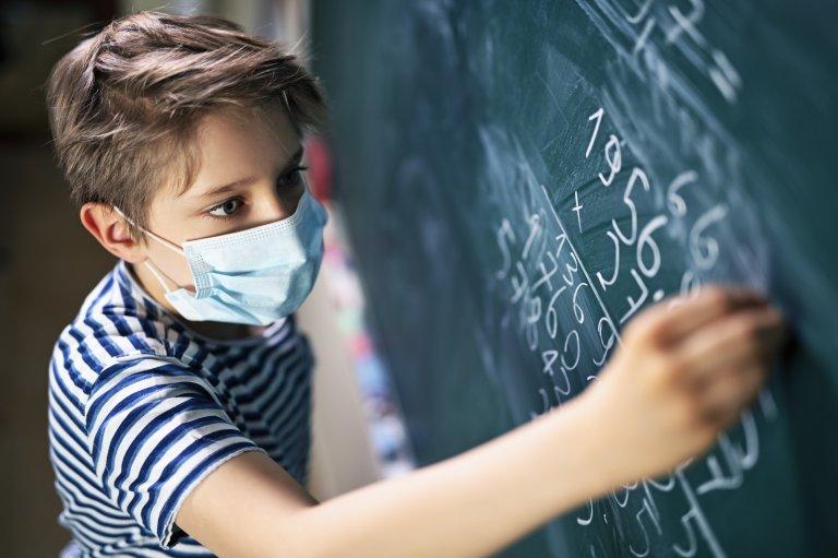 Boy in mask at chalkboard
