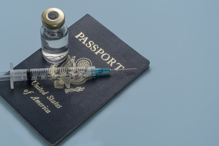 Photo fo a U.S. passport with a vaccine bottle and syringe