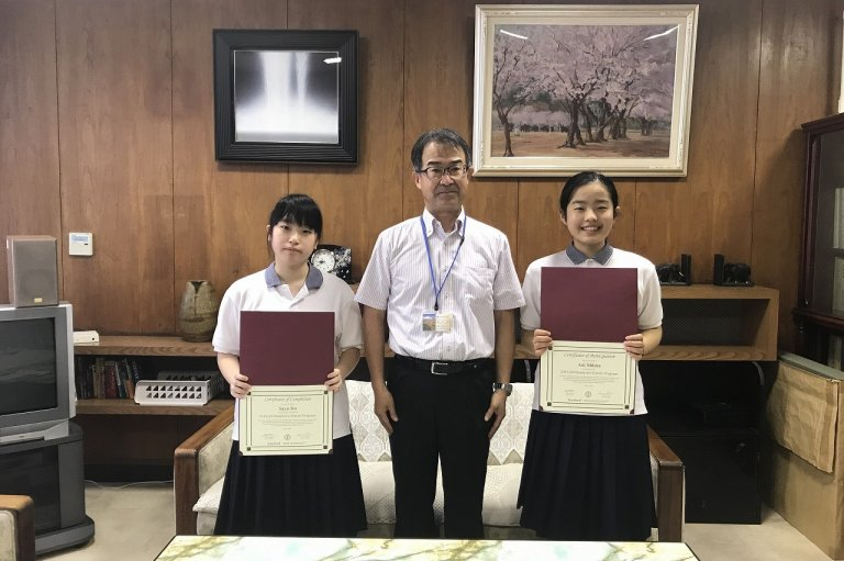 Two students holding diplomas with a principle in a room