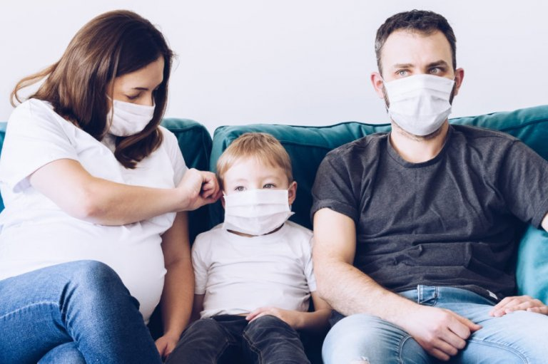 Family sits on couch with masks