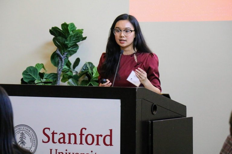 Student in a red dress presenting at a podium with Stanford signage