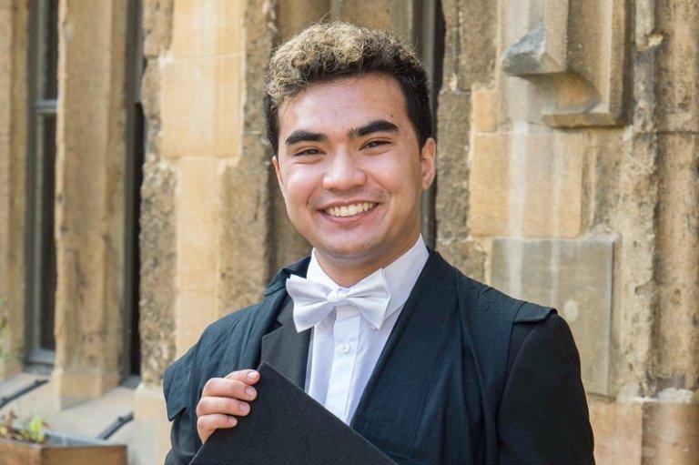 Josh Cobler holding graduation cap