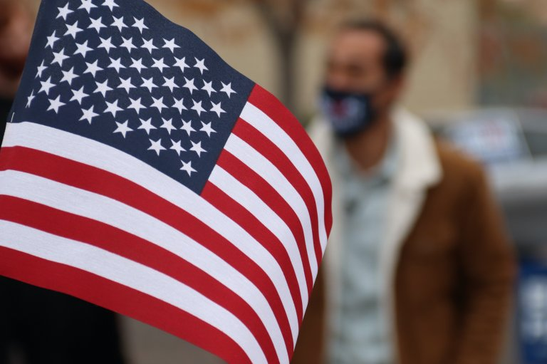 Picture of small American flag in front of a man in a mask.