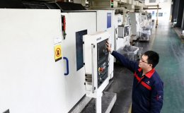 Chinese worker examines panel on machinery