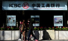 Pedestrians walk past a Madrid branch of the Industrial and Commercial Bank of China (ICBC), one of the largest state-owned enterprises in China.