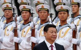 Chinese People's Liberation Army navy soldiers of a guard of honor look at Chinese President Xi Jinping