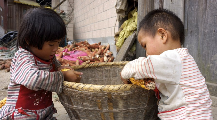 Young children sort corn outside of a home in a rural village in China.