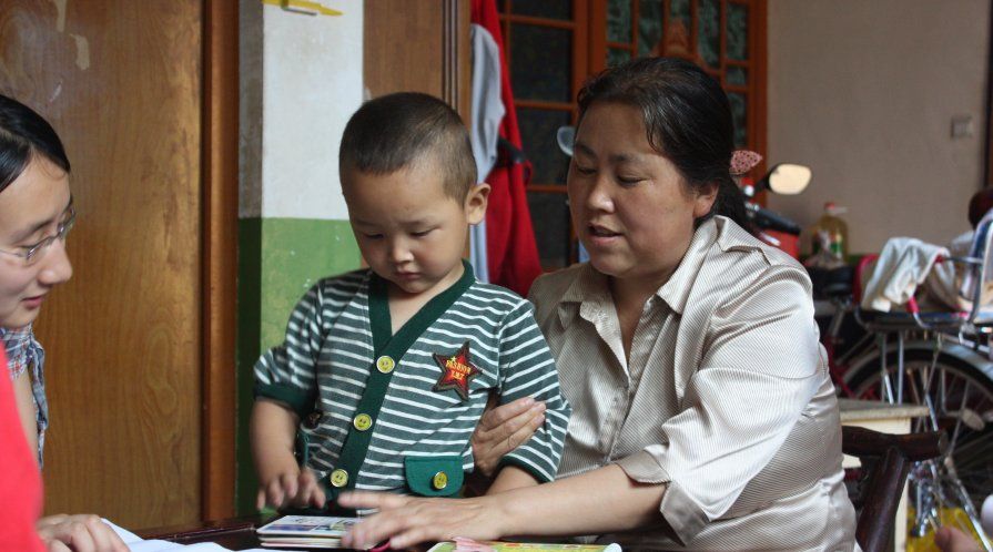 A toddler and his caregiver looking at a book together at a table in a home.