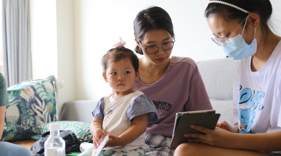 Migrant child sits on her mother's lap, looking into the camera, as her mother reviews REAP's survey forms with an enumerator.