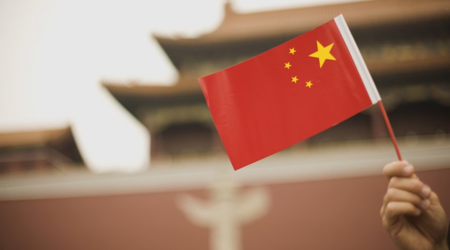 Handheld Chinese flag in front of a government building in Beijing, China.