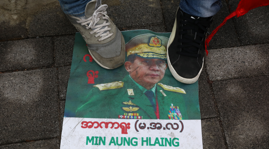 Protesters in Myanmar stand on a picture of General Min Aung Hlaing