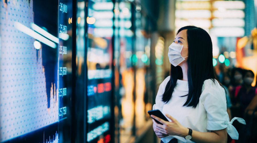 Woman in a face mask looking at a stock market board