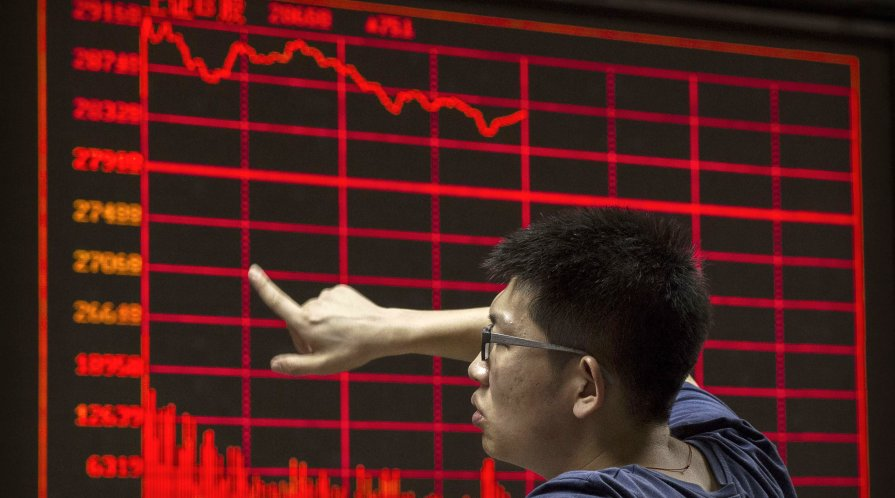 A Chinese day trader reacts as he watches a stock ticker at a local brokerage house on August 27, 2015 in Beijing, China