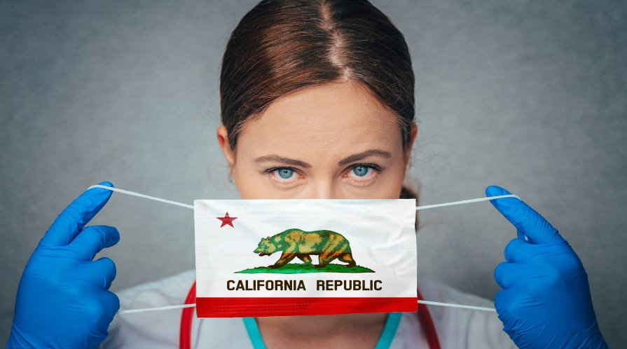 Women doctor holds a surgical mask with the California Republic flag.