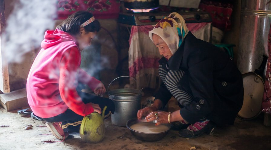 A mother and child preparing food inside a yurt in rural China.