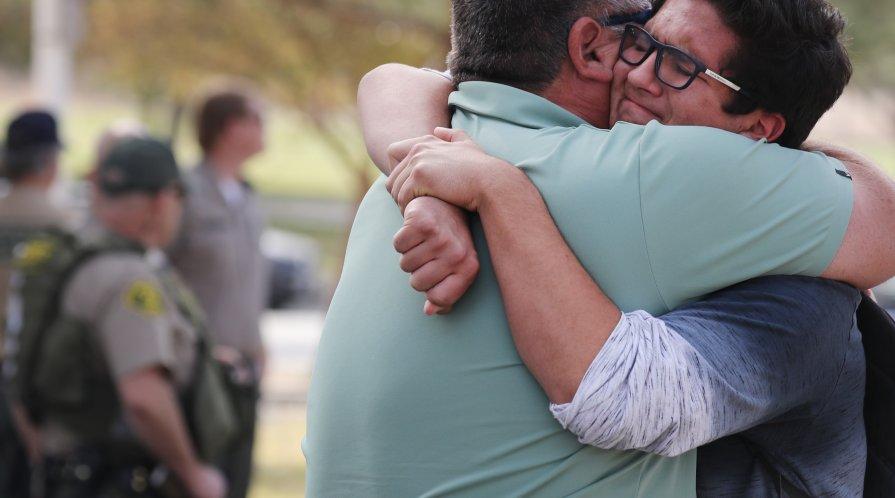 A boy hugs his father after a school shooting in Santa Clarita, CA.