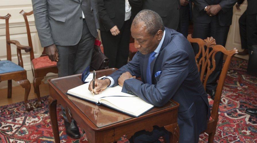 Le président guinéen Alpha Condé signe le livre d'or du Secrétaire d'Etat américain John Kerry