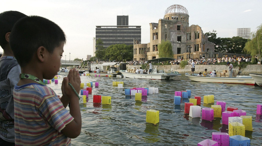 A young boy prays after releasing a floating lantern onto the Motoyasu River in front of the Atomic Bomb Dome in Hiroshima, Japan.