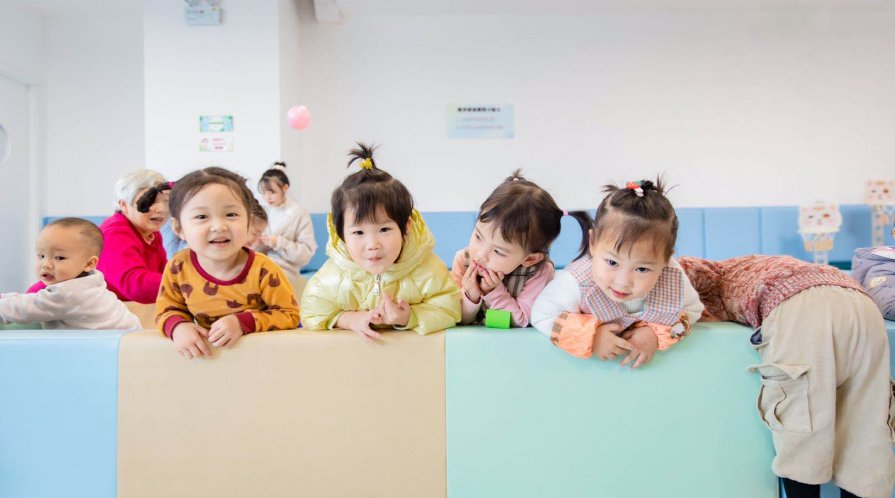 Toddlers pose for a picture at a brightly colored parenting center in Sichuan, China.