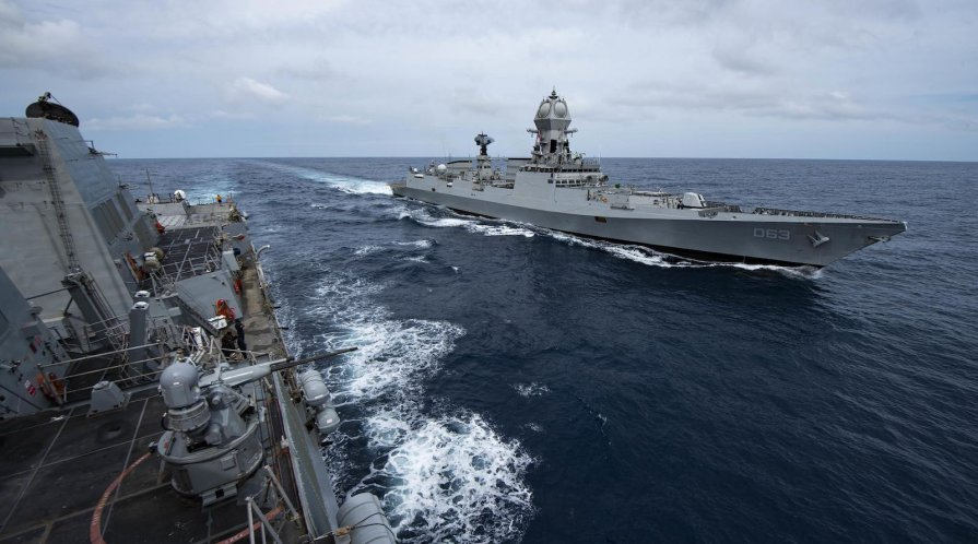Two destroyer navy ships sail alongside each other