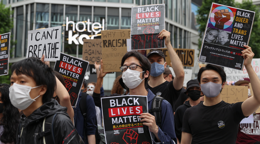 Protesters hold signs and chant slogans during a Black Lives Matters Peaceful March on June 14, 2020 in Tokyo, Japan.