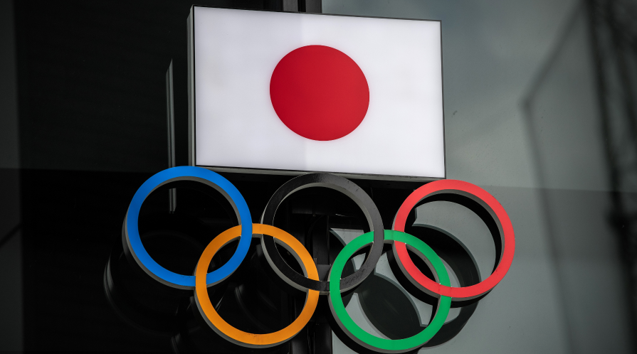 The flag of Japan is displayed over the Olympic rings.