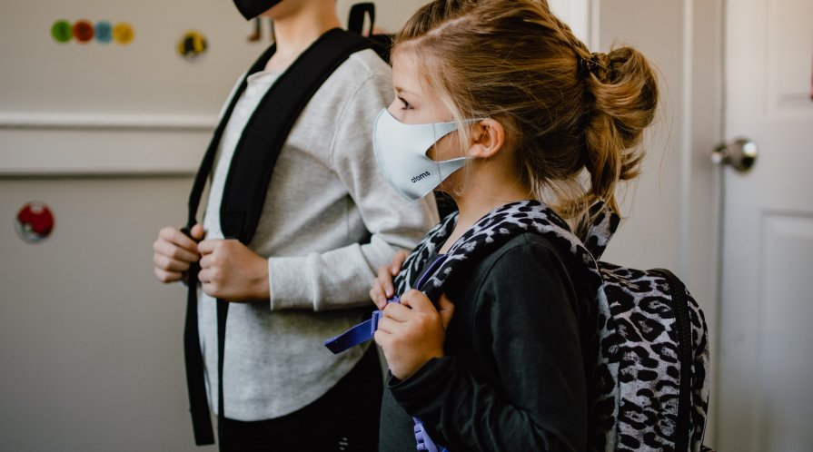 A young girl heads back to school with a mask.