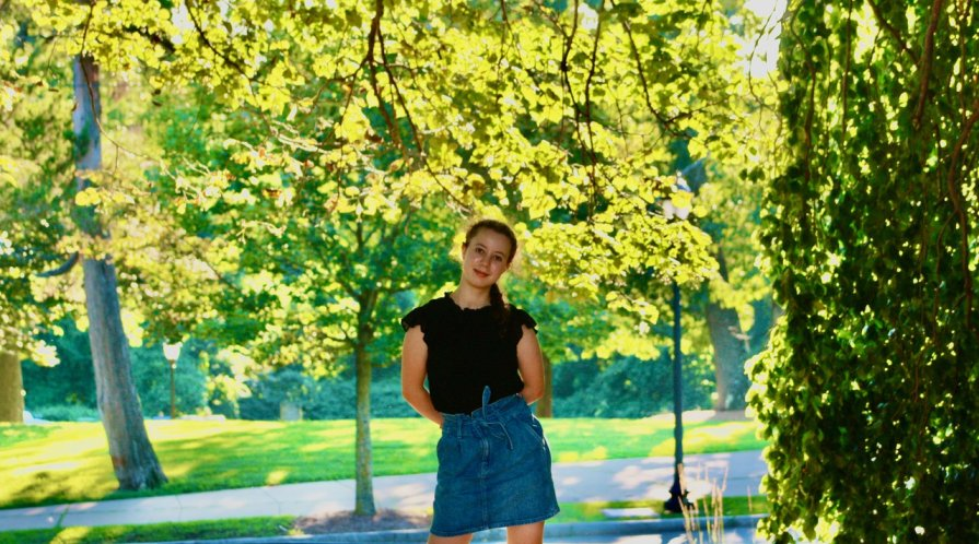 high school girl standing amidst park greenery