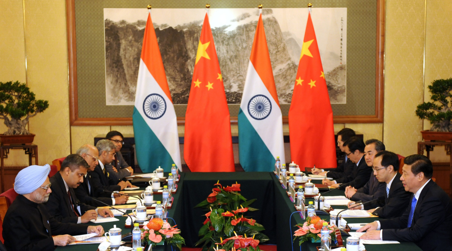 Chinese President Xi Jinping (R) talks with India's Prime Minister Manmohan Singh (L) during a meeting at the Diaoyutai State Guesthouse in 2013.