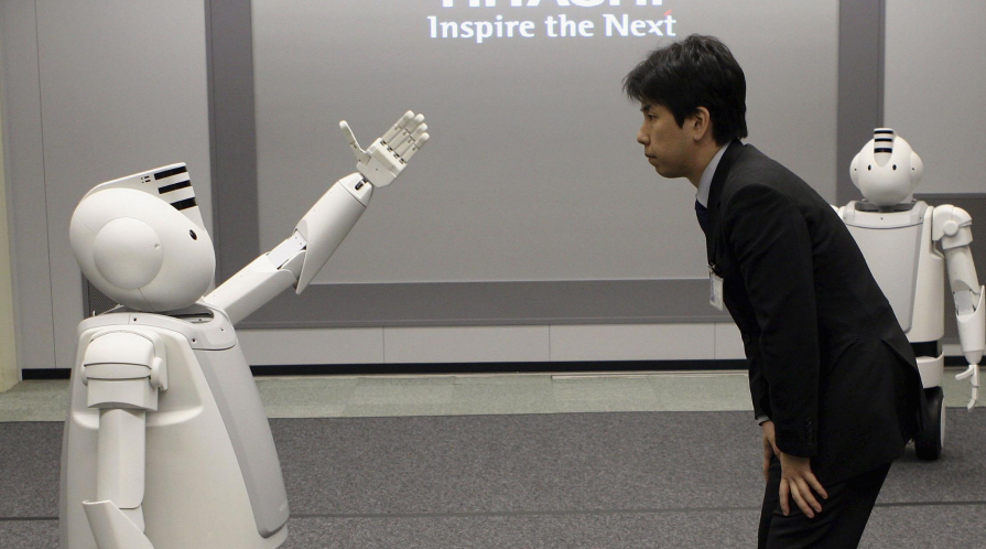 A man with interacts with 'Emiew,' a humanoid robot.