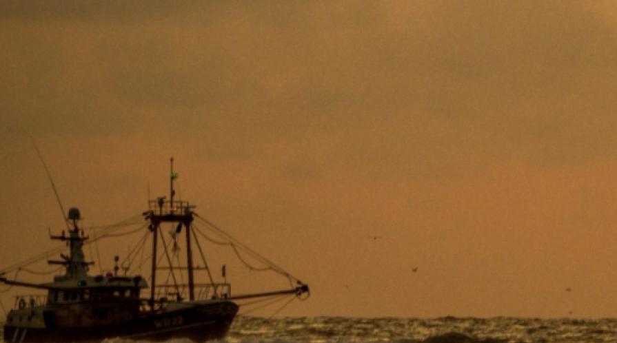 A fishing boat at sea under a hazy sky
