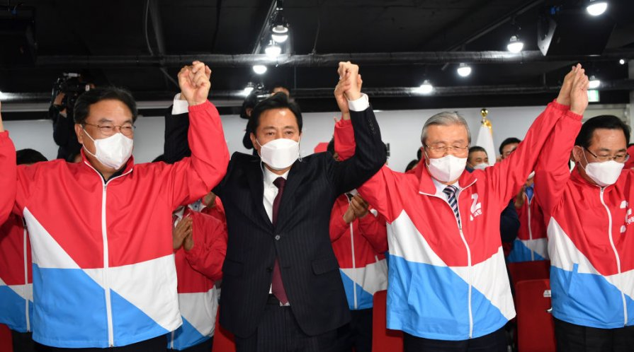 South Korean men standing up, wearing face masks, holding hands and cheering