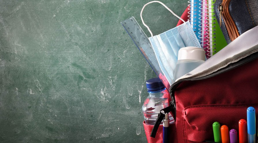 A surgical mask is tucked into a pupil's school backpack.