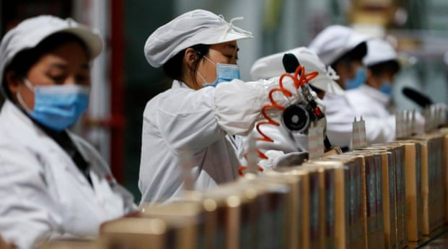 Workers on the assembly line in the packaging workshop of a liquor enterprise, Sihong county, Jiangsu province, China.