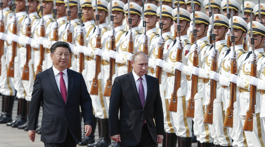 Photograph of Xi Jinping and Vladmir Putin walking in front of two lines of armed Chinese soldiers