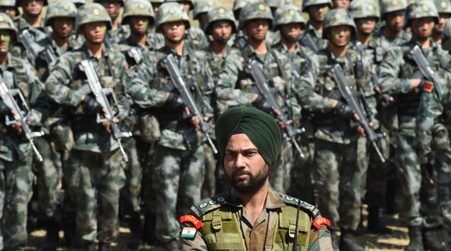 An Indian Army soldier stands in front of a group of People's Liberation Army troops during joint drills