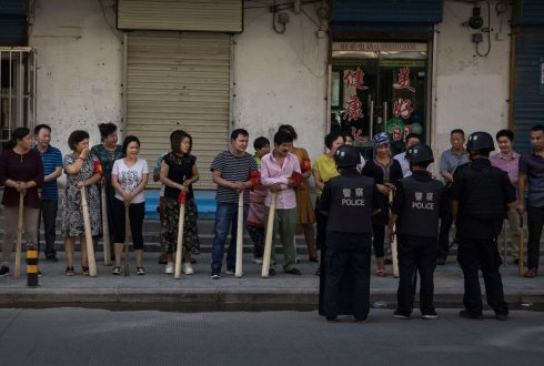 A mix of ethnic Uyghur and Han shopkeepers hold large wooden sticks as they are trained in security measures on June 27, 2017 next to the old town of Kashgar, in the far western Xinjiang province