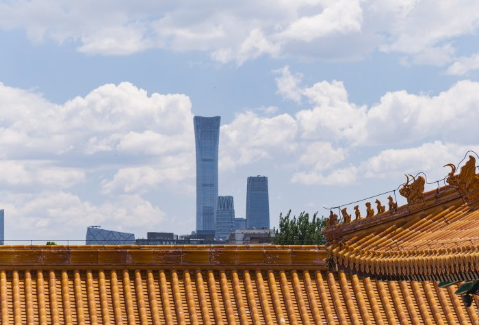 View of building roof in the Forbidden City complex and the Beijing skyline in the background
